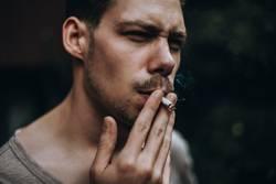 Junger Mann zieht an einer selbstgedrehten Zigarette