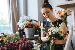 Floristin bindet einen bunten Strauß Blumen