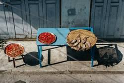 Fisch und rote Chilischoten trocknen auf einem blauen Tisch