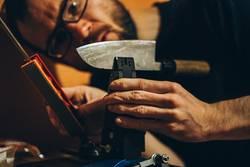 Mann schärft ein japanisches Küchenmesser