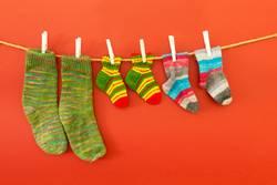 Bunte Socken an einer Wäscheleine auf rotem Hintergrund