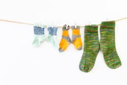 Bunte Socken an einer Wäscheleine auf weissem Hintergrund