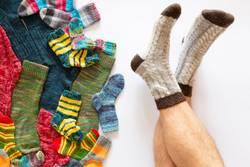 Bunte Socken auf weissem Hintergrund und ein Paar Männerbeine