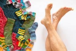 Bunte Socken und ein Paar nackte Beine auf weissem Hintergrund