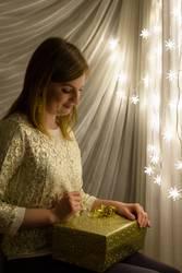 Junge Frau mit Geschenk vor einer leuchtenden Weihnachtskette