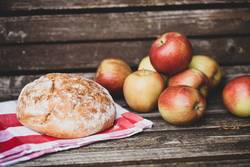 Laib Brot und knackige Äpfel auf Holzbank