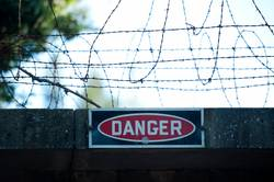 danger sign under barbed wire fence