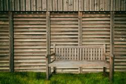 Gartenbank an einem Holzzaun