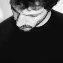 Junger Mann mit Bart guckt traurig runter