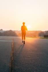 Frau joggt in einen Sonnenaufgang
