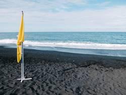 Gelbe Fahne am windstillen Strand