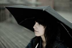 woman sitting with an umbrella waiting for somebody