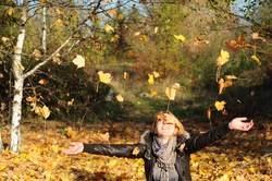 Young woman enjoying falling autumn leaves in park