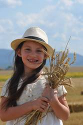 smiling little girl holding wheat in hands