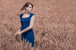 Autumn beauty in cornfield with blue dress
