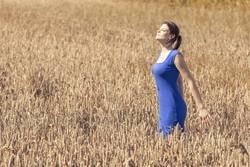 Junge Frau mit blauem Kleid genießt Herbst Sonne im Kornfeld
