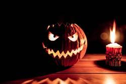 Gruseliger geschnitzter Halloween Kürbis neben brennender Kerze