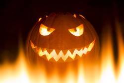 Gruseliger geschnitzter Halloween Kürbis in Feuer Flammen brennt