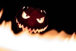 Spooky smiling halloween pumpkin in hot burning hell fire flames