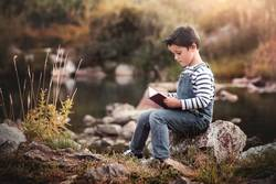 Child sitting reading a book in the field
