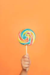 Child's hand with Colorful lollipop