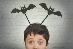 funny child with halloween vampires over on his head