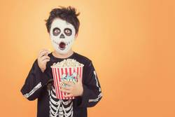 Surprised child in a skeleton costume with popcorn