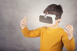 boy playing with virtual reality glasses on gray background