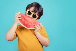 Happy child with sunglasses eats watermelon