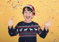 smiling child with confetti Wearing Christmas Santa Claus Hat