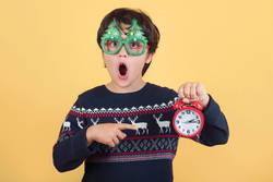 Surprised child with alarm clock Wearing Funny Christmas glasses