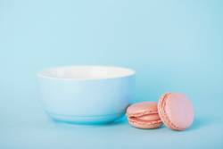 Raspberry pastel pink macarons next to a blue bowl
