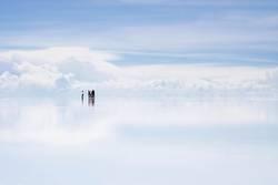 Gruppe von Menschen steht im Uyuni Salzsee vor Wolken