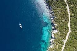 Segelboot ankert in felsiger Bucht mit türkisblauem Wasser