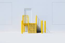 Yellow staircase with an entrance door and a white wall