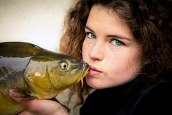 Young woman with impressive green eyesvkissing a carp, fish