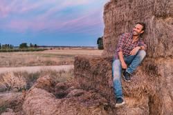 Ein glücklicher Mann sitzt auf einem Haufen Heu.
