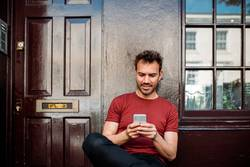Mann sitzt auf einer Bank auf einem schönen kastanienbraunen Hintergrund.