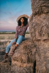 Glückliche schwarze junge Frau, die auf einem Haufen Heu sitzt.