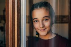 Porträt eines jungen Teenagermädchens, das durch das Fenster schaut.