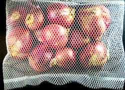 Red onions in mesh bag isolated on black background