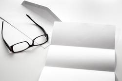 blank of letter paper and envelope with eyeglasses