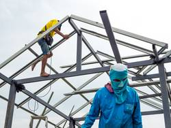 Workers working in the construction site to build a house