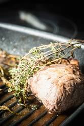 Ein Stück Fleisch frisch aus dem Ofen mit einem Zweig Thymian