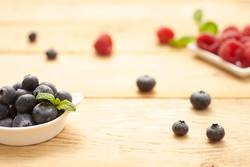 fresh and raw blueberries and raspberries on wooden background