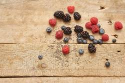 different fresh berries on rustic wooden background