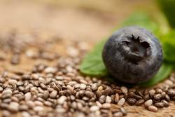 close up of blueberry with chia seeds an leaf of mint