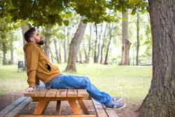 Man sitting in a park, on a picnic table