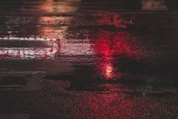 wet asphalt with red light reflection