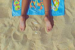 feet of a person lying on a towel on the beach, top view